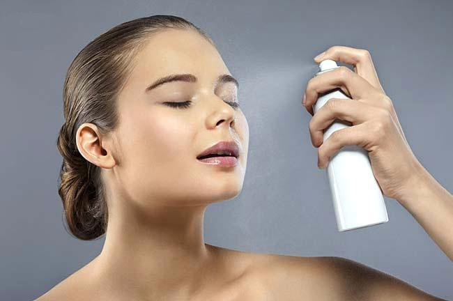 A woman spraying her face with hydrating spray