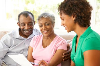 Senior Couple Talking To Financial Advisor At Home