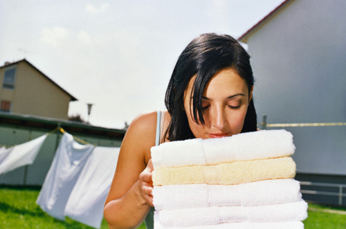Woman Smelling Clean Towels