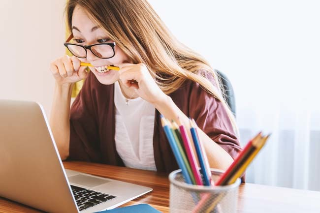 women biting pencil